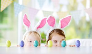 two little kids wearing bunny ears and playing with easter eggs at an easter party