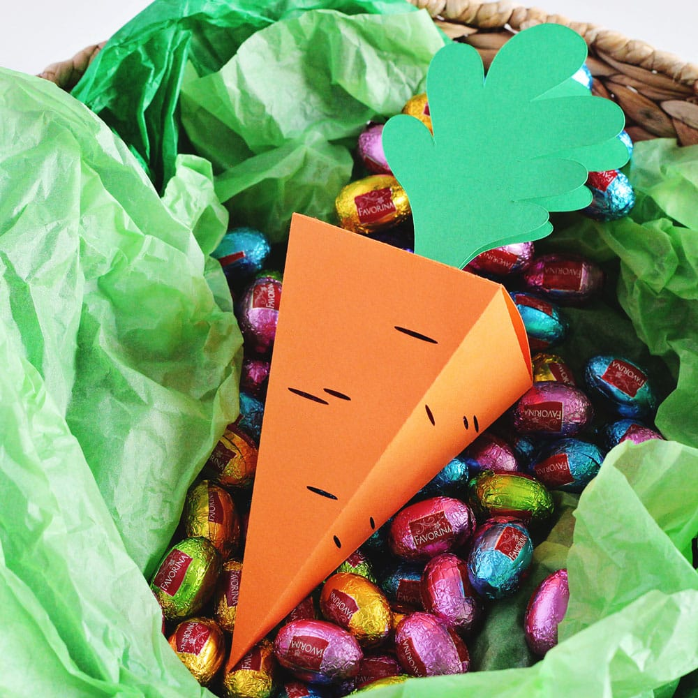DIY Easter carrot treat box sitting in a basket surrounded by mini foil wrapped chocolate eggs