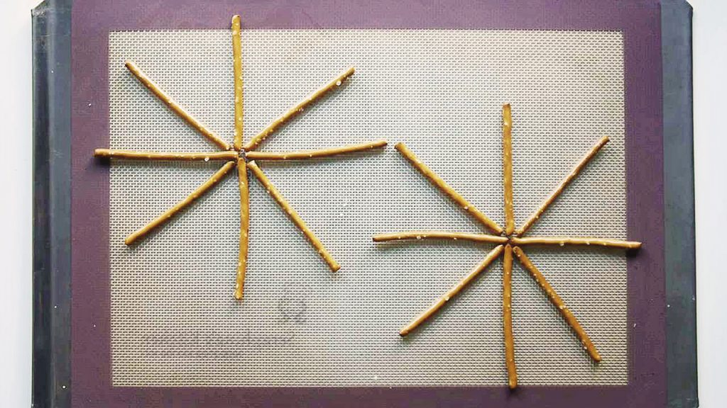 pretzel sticks arranged in a radial formation on a silicone mat
