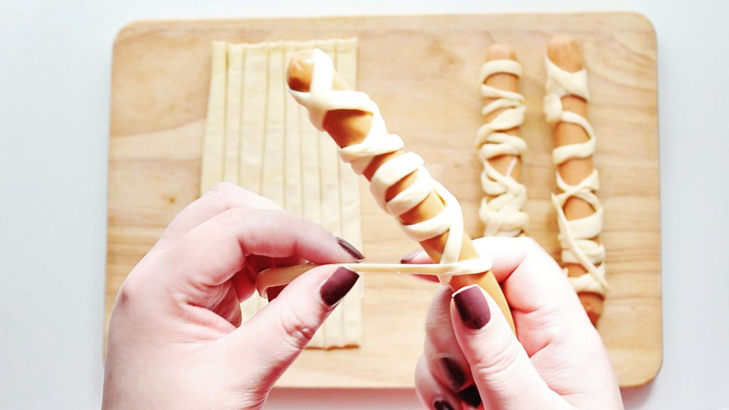 wrapping hot dogs with crescent roll strips to make mummy hot dogs