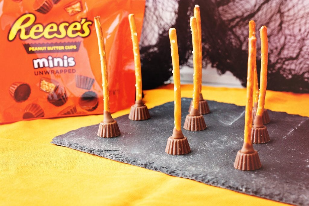 Reese's peanut butter cups and pretzel broomstick treats on black slate serving plate with a packet of mini Reese's peanut butter cups in the background