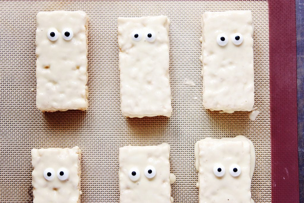 top view of rice krispie treats dipped in white chocolate with candy eyes, laid out on a baking sheet