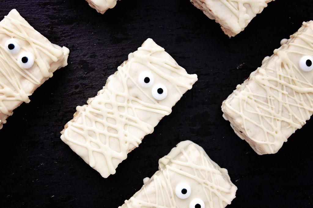 flat lay of Halloween mummy rice krispie treats on a a dark background