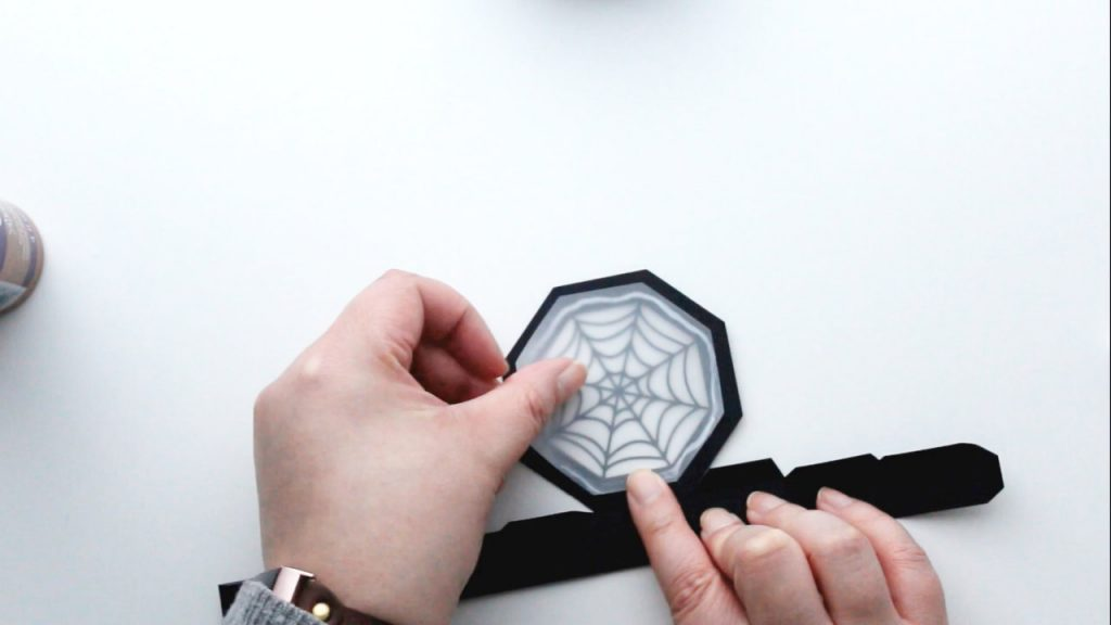 carefully place the backing piece over the spider web on the inside of the lid and smooth down