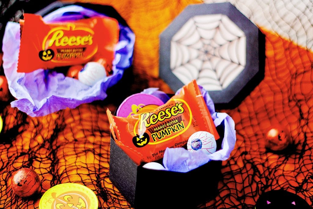 two black spiderweb treat boxes filled with chocolate Halloween treats