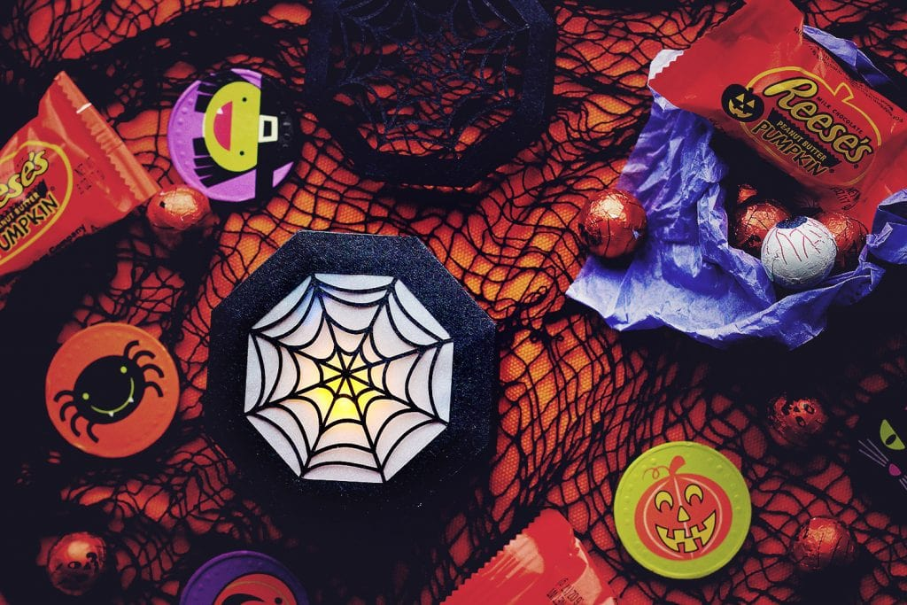 top view of the closed spider web treat box being ussed as a lantern with an led tea light inside
