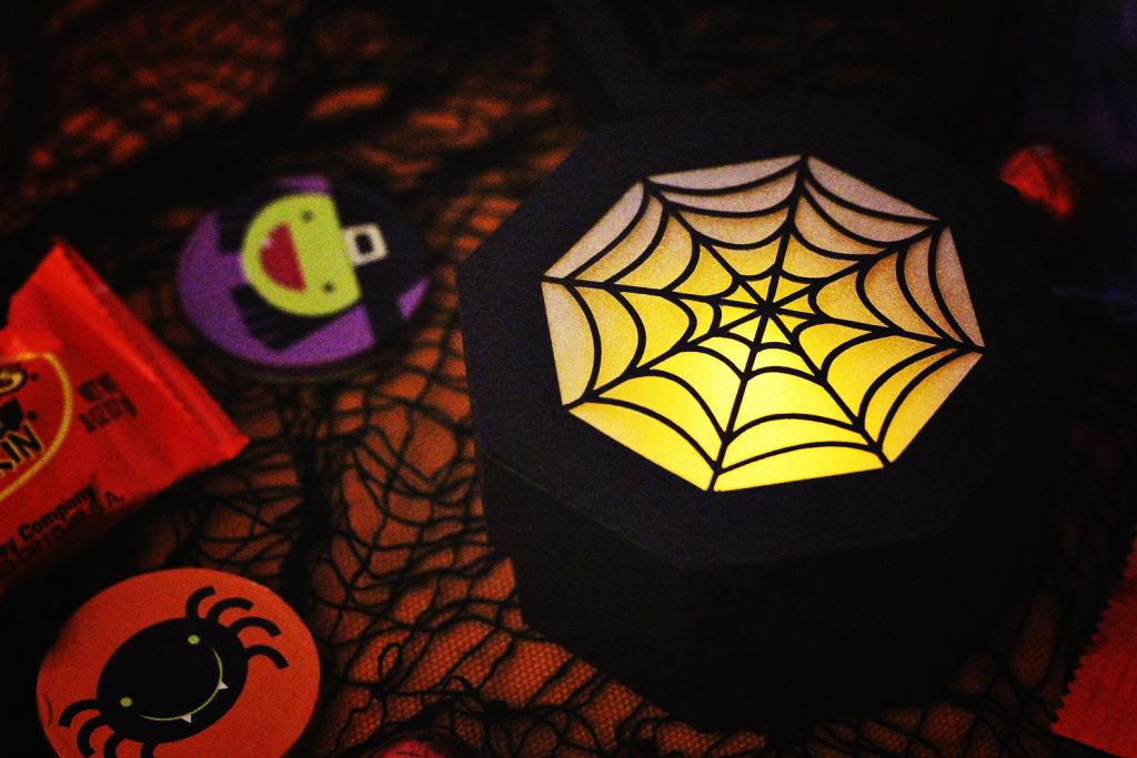 close up of the closed spider web treat box being used as a lantern with an led tea light inside for easy DIY halloween decor