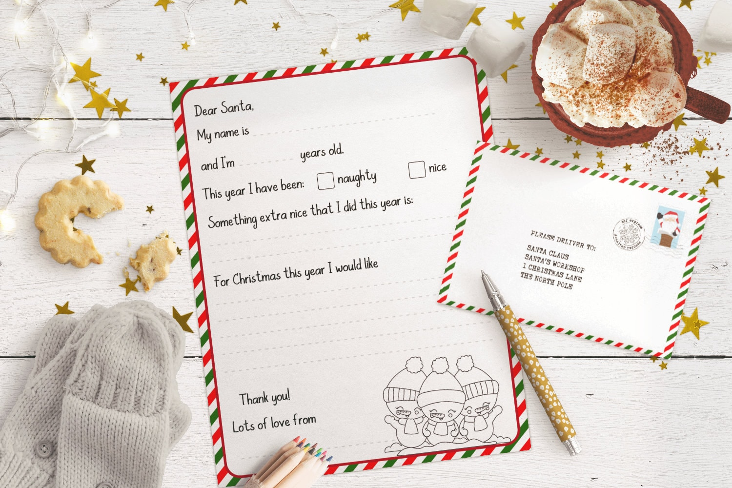 Letter to Santa printable and matching envelope on a white wood table, with fairy lights, hot cocoa and gold stars in the background