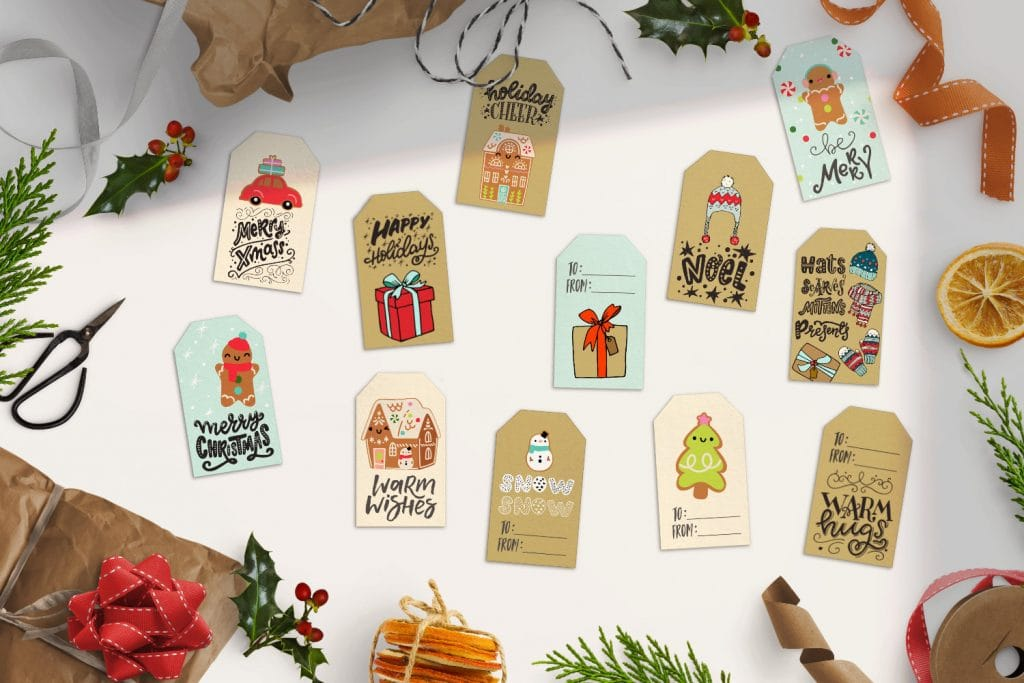 top view of 12 cute free printable Christmas gift tags lying on a white table surrounded by gift wrap, holly and, ribbon, dried oranges and leaves
