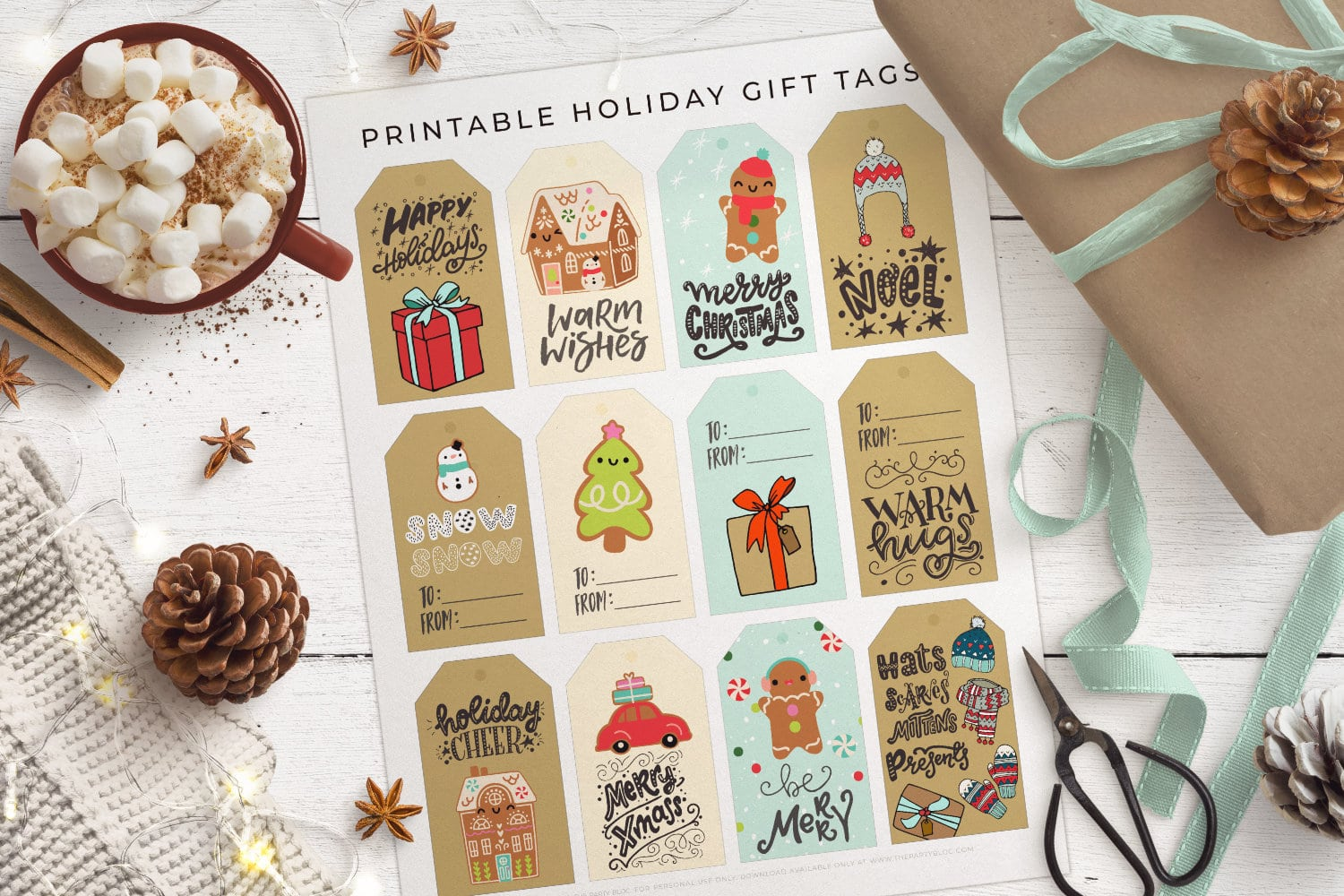 top view of full sheet of printed christmas gift tags on a white wood table, with a wrapped gift, ribbons, hot chocolate and christmas decor