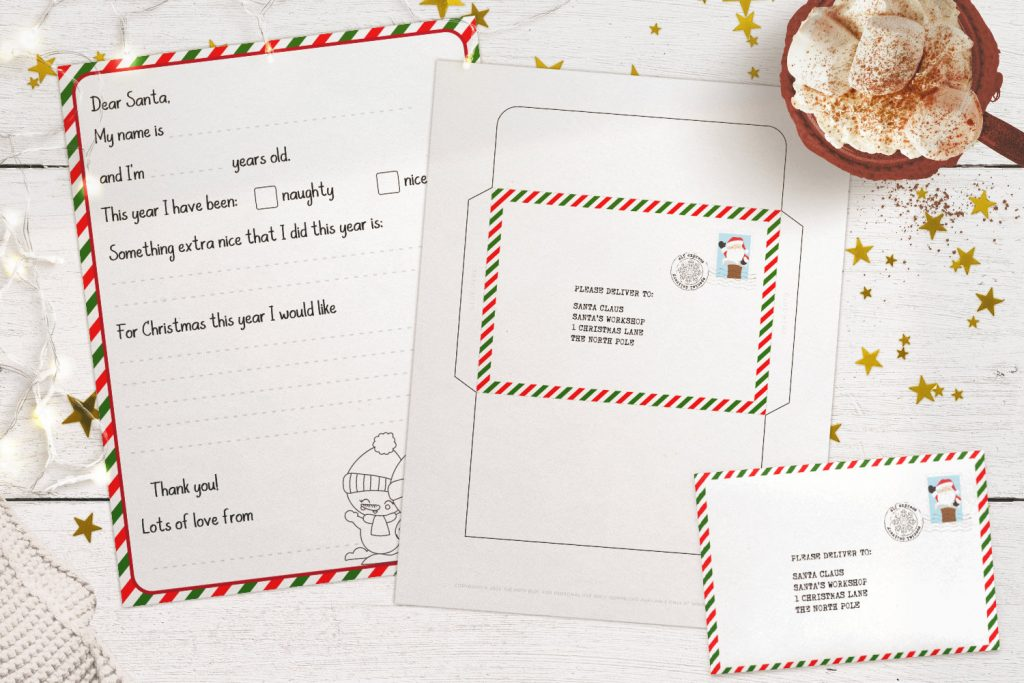 Letter to Santa printable template and matching envelope on a white wood table, with fairy lights, hot cocoa and gold stars in the background