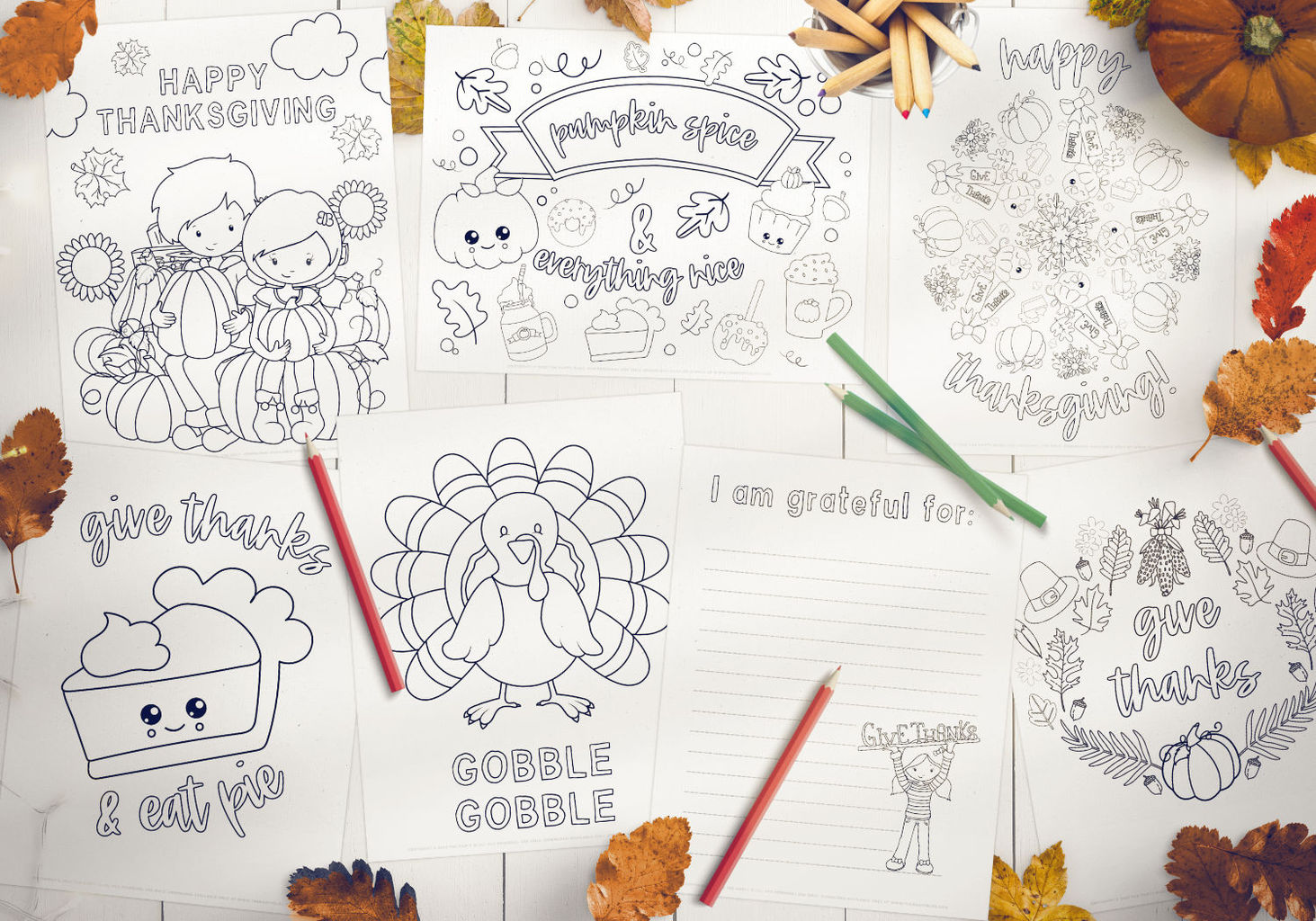 7 Thanksgiving themed coloring pages spread out on a white wood background with fall leaves, pumpkins and color pencils scattered around