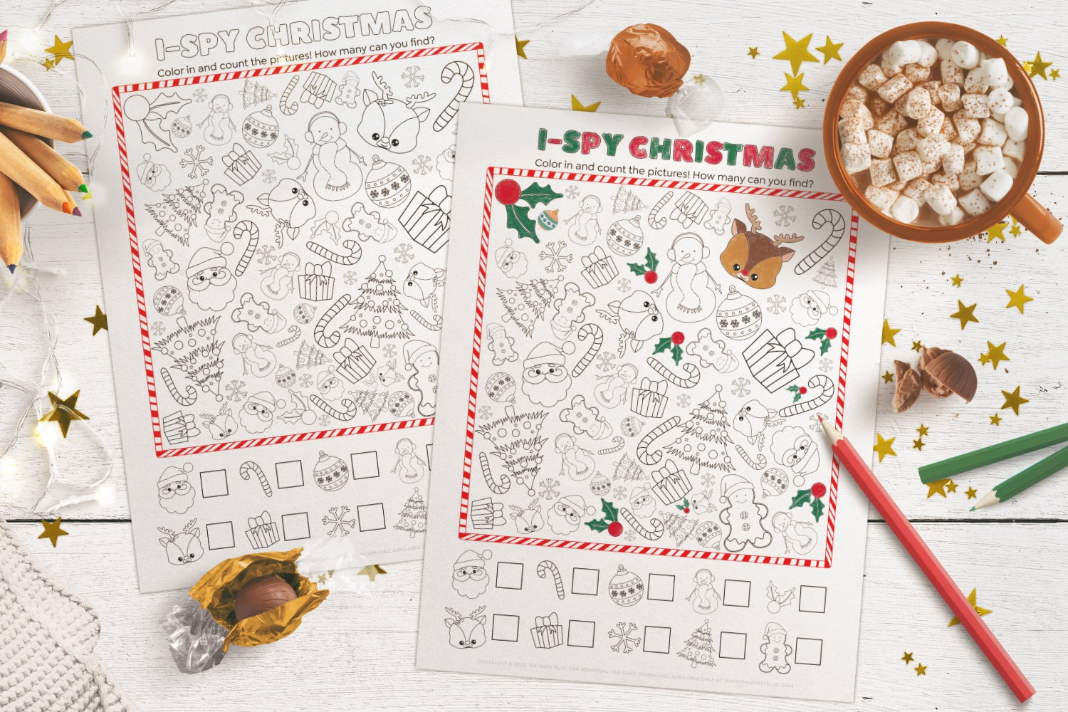 top view of two christmas i-spy activity printable sheets on a white table, the top sheet is partially colored in