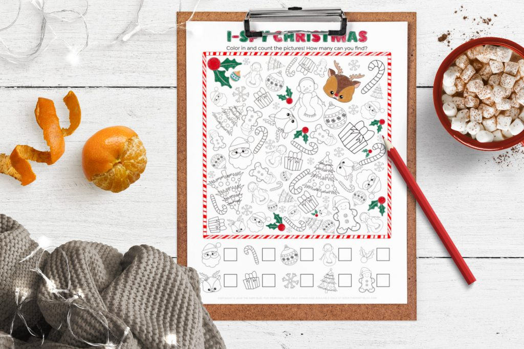 top view of the christmas i-spy activity printable on a clipboard, partially colored in