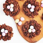close up flat lay of chocolate Easter nests on a wood board with candy mini eggs scattered around