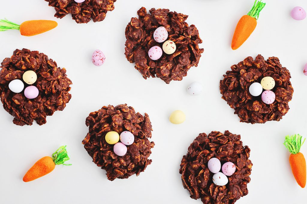 flat lay of chocolate Easter cornflake nests on a white table surrounded by scattered chocolate mini eggs and carrot decorations