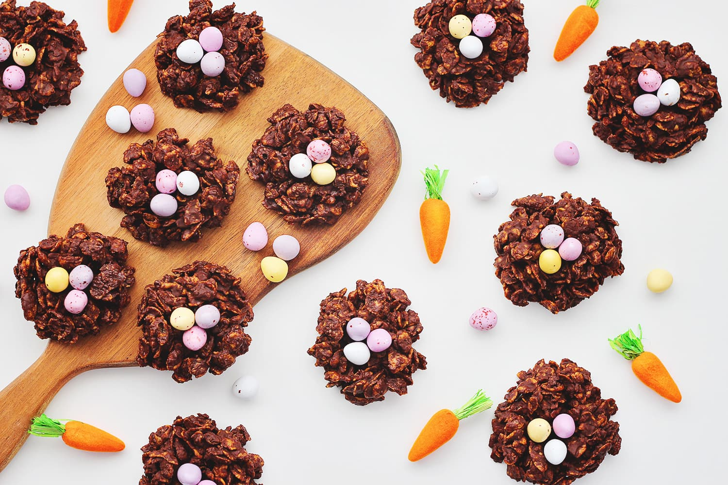 flat lay of Easter chocolate nests on a white table with mini chocolate eggs and carrot decorations scattered around