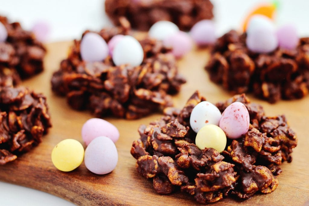 close up of chocolate and cornflake Easter nest cookies on a wood board