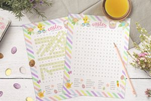 Free Easter word search printable on a table with the answer sheet, a pencil, surrounded by flowers and mini chocolate eggs