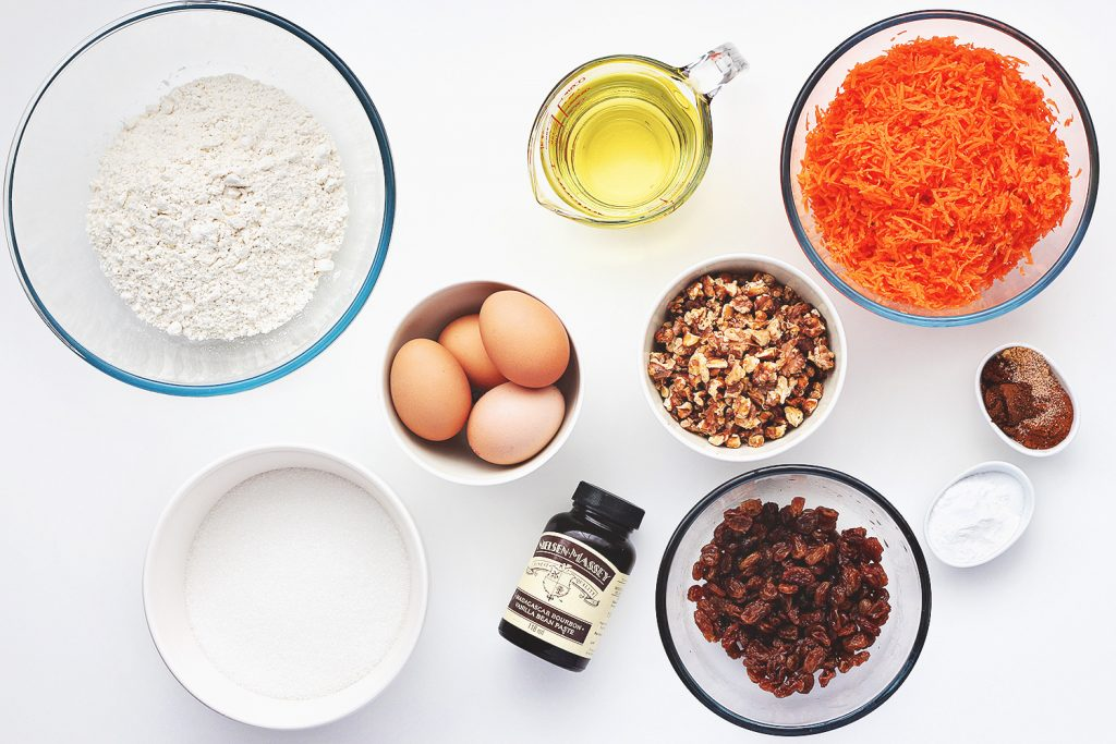 Flat lay of the ingredients needed to make the carrot cake in bowls on a white table