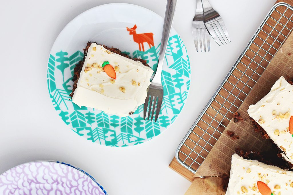 Flat lay of a slice of carrot cake on a teal pattern plate with a fork, surrounded by more slices of cake and plates