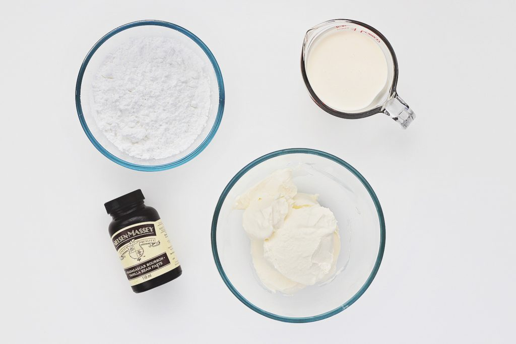 Top view of a white table with ingredients for whipped cream cheese frosting laid out.
