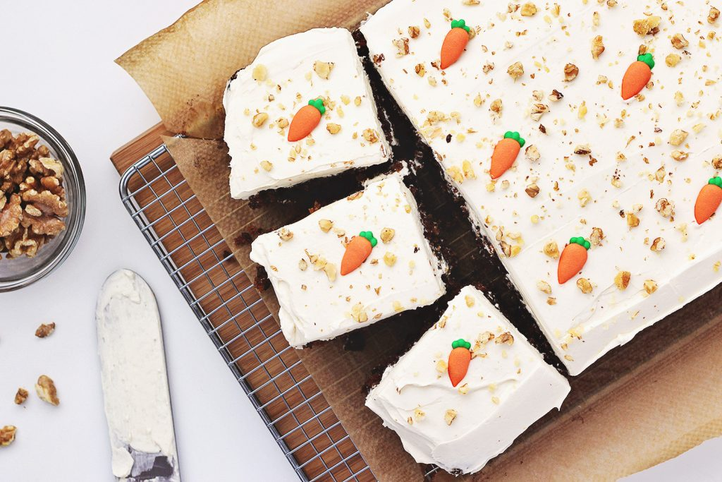 Flat lay of carrot cake decorated with candy carrot decorations and chopped walnuts. Three slices are cut out of it, and there is a small dish of chopped walnuts and a palette knife covered in cream cheese frosting on the table.