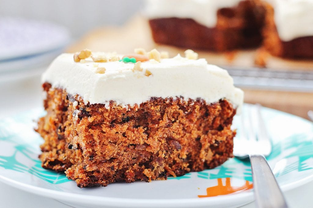 Close up of a slice of carrot cake on a teal patterned plate with a fork, and the rest of the cake in the background