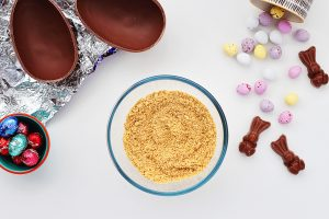 Top view of a white table with a small glass bowl containing crushed digestive biscuits, or graham crackers. The bowl is surrounded by a halved chocolate egg and Easter candy.