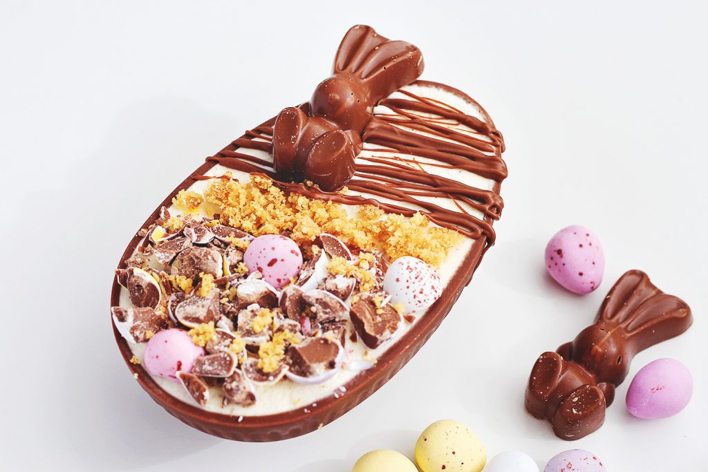 No-bake vanilla cheesecake in a chocolate egg shell decorated with Easter candy and melted chocolate