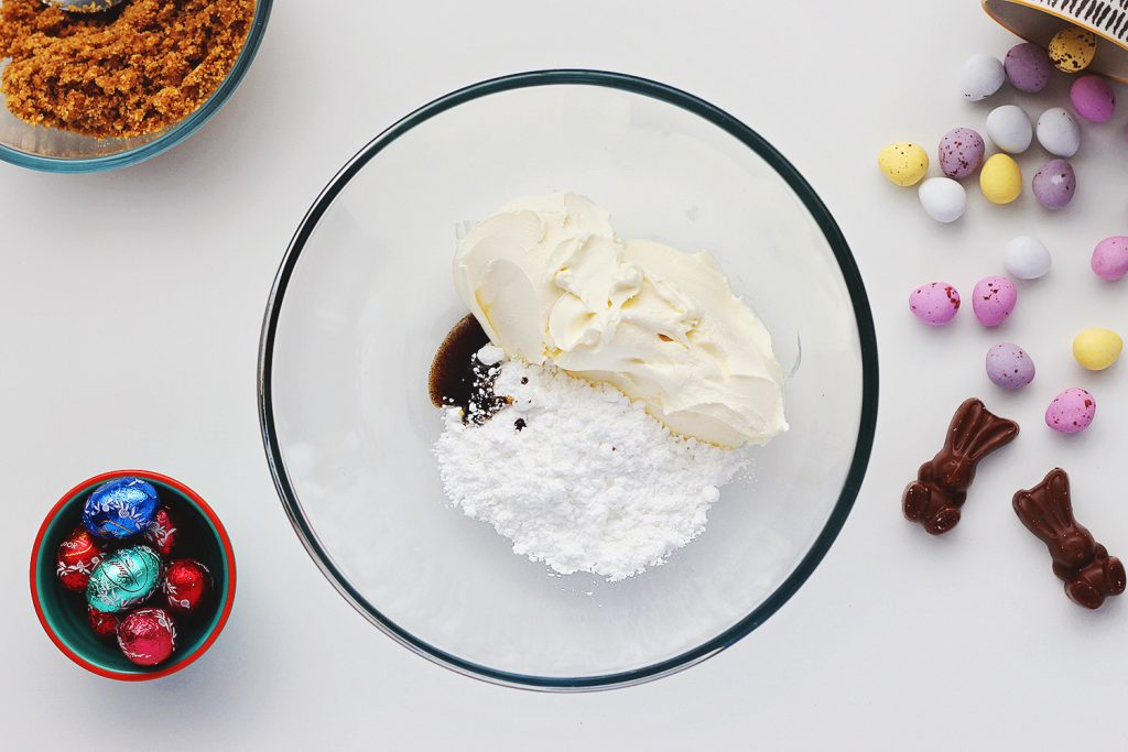 Top view of a glass bowl containing vanilla, cream cheese and powdered sugar mixed together. The bowl sits on a white table and is surrounded by ingredients for the no-bake Easter egg cheesecake