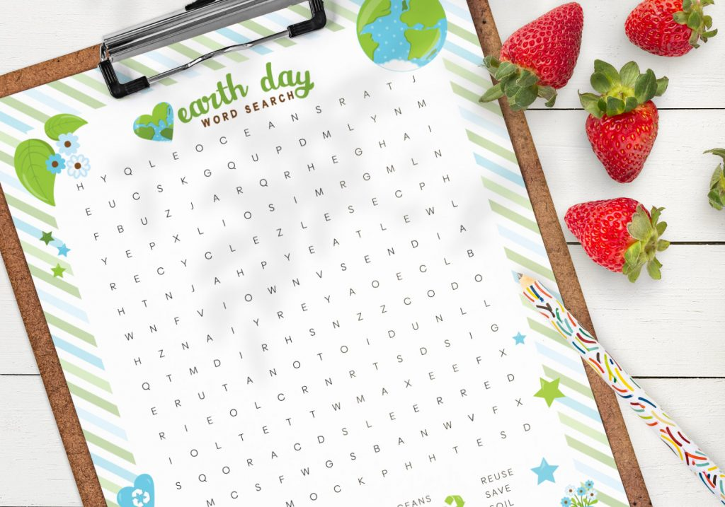 Close up of the free printable earth day word search on a clipboard lying on a table, with a colorful pencil and some strawberries