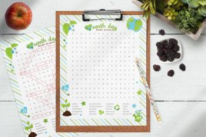 Table with the free printable Earth Day word search on a clipboard. The answer sheet is behind the clipboard. There's a box of succulents, blackberries and an apple surrounding the word search sheets